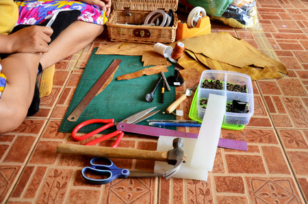 key punching: Thai woman punching hole and cutting for made handmade bag leather and key ring at home in Nonthaburi, Thailand. Stock Photo