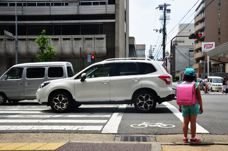 Children japanese girl waiting cross over road at crosswalk traffic road near Gojo subway station on July 11, 2015 in Kyoto, Japan