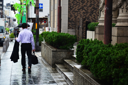 bussiness time: Bussiness japanese man walking go to office near at Nara station while raining time on July 7, 2015 in Nara, Japan