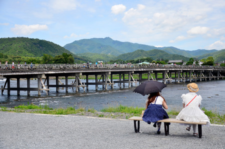 looking at view: Japanese women sit and looking view of Togetsukyo Bridge and Oi River at Arashiyama on July 12, 2015 in Kyoto, Japan