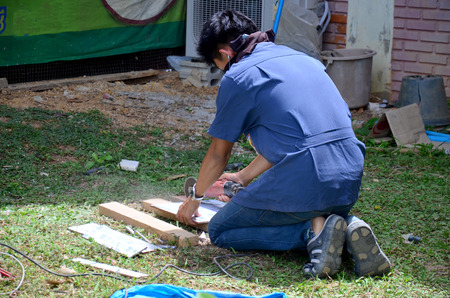 cornerstone: Man use cutting machine cut quarry tile at garden August 29, 2015 in Phrae, Thailand