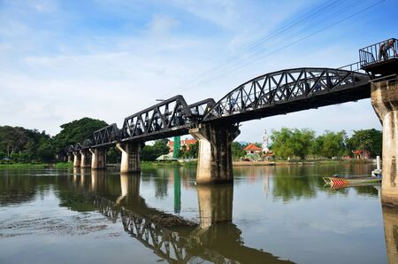 People travel and walking at the Bridge of the River Kwai. Internationally famous, black iron bridge was built from by Japanese supervision by Allied prisoner-of-war labour as part of the Death Railway linking Thailand with Burma in Kanchanaburi, Thailand Reklamní fotografie