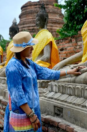 chaimongkol: Thai woman portrait with buddha statue of Wat Yai chaimongkol in Ayutthaya, Thailand Stock Photo