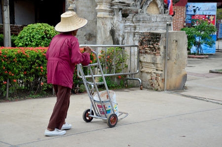 groundskeeper: Old man working keep garbage at Wat Yai chaimongkol on October 9, 2015 in Ayutthaya, Thailand Editorial