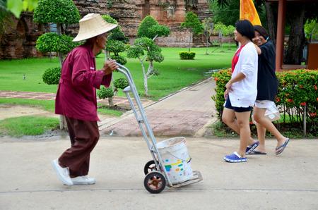 groundskeeper: Old man working keep garbage at Wat Yai chaimongkol on October 9, 2015 in Ayutthaya, Thailand Editorial