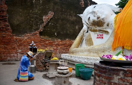 thai buddha: Thai people pray with flower, joss stick and candle for Reclining Buddha Statue at Wat Yai chaimongkol in Ayutthaya, Thailand