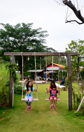 playing the market: Thai children playing swing in garden at market fair on November 29, 2015 in Nakhon Ratchasima, Thailand. Editorial