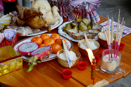 People putting Sacrificial offering food for pray to god and memorial to ancestor in Chinese new year day at home on February 7, 2016 in Nonthaburi, Thailand.