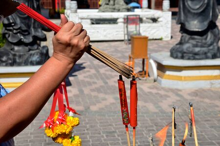 worship god: People burning incense and red candle for pray god at Suphanburi city pillar shrine in Suphanburi, Thailand. Stock Photo