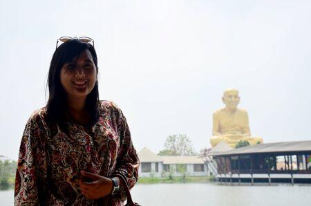 pu: Thai waman portrait with Biggest statue of Luang Pu Thuat at Buddha Uttayarn Maharach in Ayutthaya, Thailand Editorial