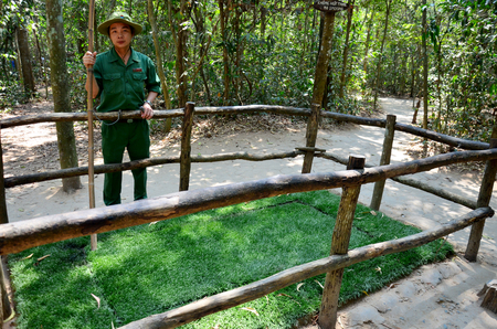 booby trap: Guides vietnamese people show A booby trap with bamboo spikes at Cu Chi tunnels on January 23, 2016 in Ho Chi Minh, Vietnam
