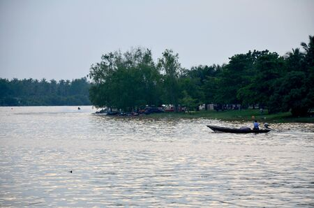 thani: Thai people driving long tail boat at Tapee river in Surat Thani, Thailand.