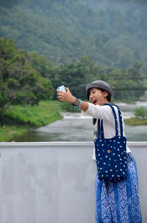 phone ban: Thai women portrait and selfie by mobile phone on bridge at Ban Khiri Wong village on September 18, 2015 in Nakhon Si Thammarat, Thailand