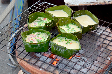 kitchen tool: Cooking Poached egg garnished with seafood or Chinese steamed eggs Thai style in banana leaf on old stove for sale at market