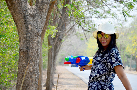 Thai woman portrait and play water gun toy at outdoor wait join with Songkran Festival is celebrated in a traditional New Year is Day at ayutthaya road in Ayutthaya, Thailand