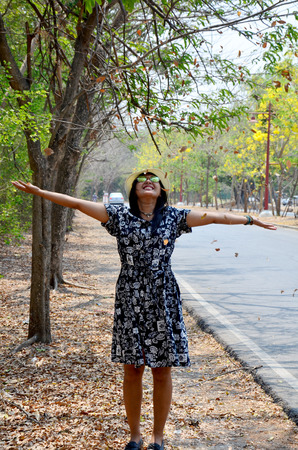 Thai woman portrait and playing throw leaf at outdoor with tree beside road of countryside in Ayutthaya, Thailand