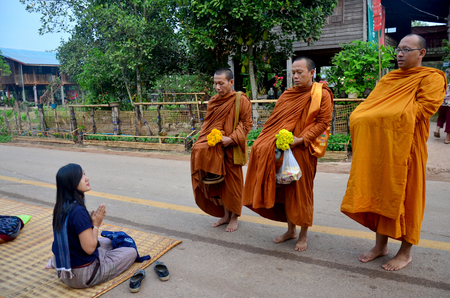 Tradition of almsgiving with sticky rice by Monks procession walk on the road for people put food offerings on January 16, 2016 in Sakon Nakhon, Thailand
