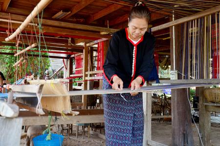 Phu Thai people using loom or weaving machine for weaving show traveller in world phutai day festival at Ban Non Hom on January 15, 2016 in Sakon Nakhon, Thailand Редакционное