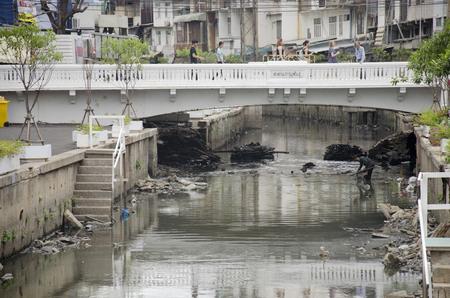 recolector de basura: Basura arquero hombre tailandés recoger la basura en submarino en aguas residuales y la contaminación del agua en el canal a la venta el 28 de junio de 2016 en Bangkok, Tailandia