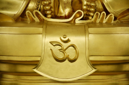 jainism: Gold word of hindu reading Om or Aum symbol in Devanagari is a sacred sound and a spiritual icon in Indian religions. It is also a mantra in Hinduism, Buddhism and Jainism. Stock Photo