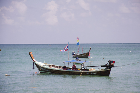 Wooden fishery boat floating and stop wait for fishing in evening time at Rawai beach at sea and ocean andaman on June 9, 2016 at Phuket, Thailand