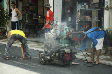 thermoplastic: Thai man working mark line thermoplastic traffic routes on the road at soi rommanee on thalang road in Phuket, Thailand