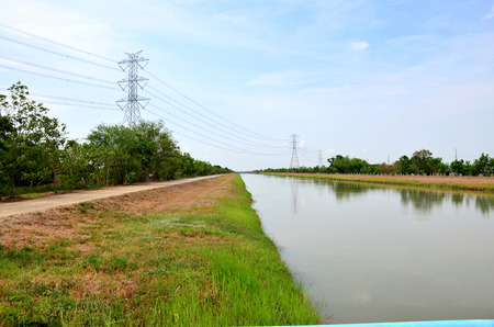 watercourse: Canal watercourse waterway of water supply with water pipehigh voltage pole in countryside Nonthaburi, Thailand