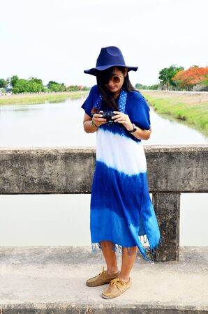 Thai woman wear clothes indigo natural color portrait at outdoor near canal watercourse waterway of water supply in countryside Nonthaburi, Thailand