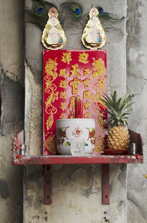joss: Chinese joss house on wall malaysian style for people pray at George Town and street art area in Penang, Malaysia Stock Photo
