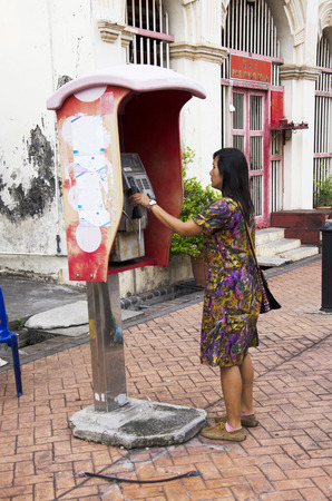 payphone: Traveller thai woman using public telephone or payphone booth call back home at George Town and street art area on April 26, 2016 in Penang, Malaysia
