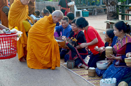 almsgiving: Traditional of almsgiving with sticky rice by Monks procession walk on the road for people put food offerings on January 17, 2016 in Sakon Nakhon, Thailand