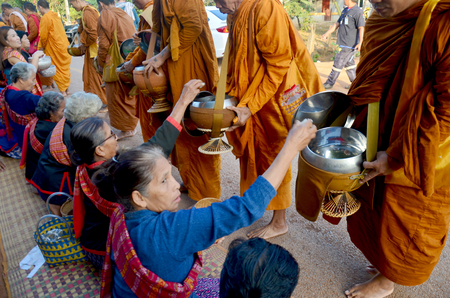 Traditional of almsgiving with sticky rice by Monks procession walk on the road for people put food offerings on January 17, 2016 in Sakon Nakhon, Thailand