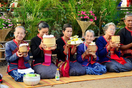 Phu tai people preparing food and almsgiving with sticky rice for put food offerings to monks procession at the road on January 17, 2016 in Sakon Nakhon, Thailand Editorial
