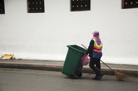cart road: Thai woman road sweeper cleaning working keep garbage and push garbage cart at the road on July 7, 2016 in Bangkok, Thailand