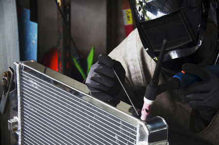 solder: Thai people use electricity welding for fix and solder radiator of car at local garage in Nonthaburi, Thailand