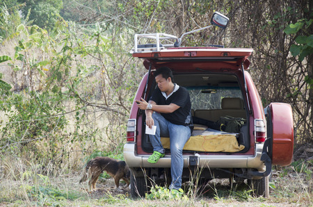 novel: Thai man people sitting on car and read novel for relax at outdoor in Ratchaburi,Thailand