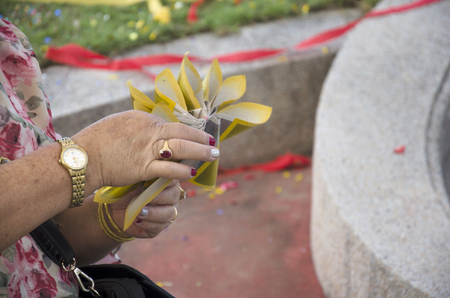 money to burn: My family prepare and folding joss paper or money paper for burn respect ancestors in the Qingming Festival at Sritasala Cemetery in Ratchaburi, Thailand. Stock Photo
