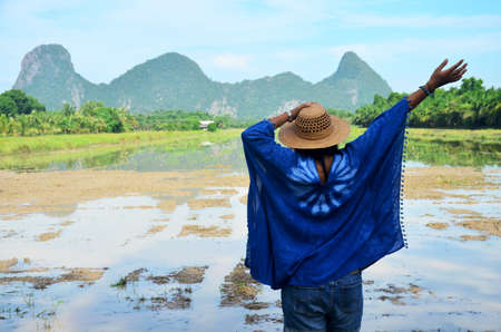 clothing model: Thai women wear clothes indigo natural color portrait at outdoor near Khao Oktalu Mountain or The Hole Mountain with rice field at Phatthalung province of southern Thailand. Stock Photo
