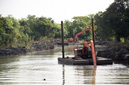 BackHoe excavator machine dredging canal at Ban Pak Pra fishing village in Phatthalung southern provinces of Thailand