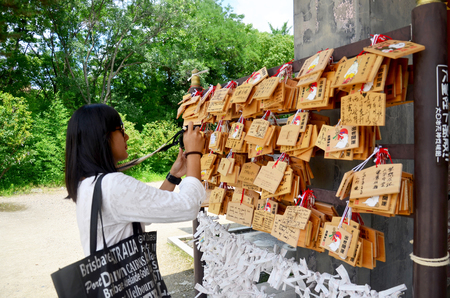 shinto: Traveler thai woman looking and shooting photo Ema Wood tag or Wooden label for pray for good luck and happy at Hokoku Shrine at Osaka Castle on July 10, 2015 in Osaka, Japan Editorial