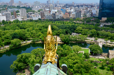 Golden dragon fish statue or Shachihoko at roof top and aerial view around Osaka castle from atop of Osaka Castle on July 10, 2015 in Osaka, Japan