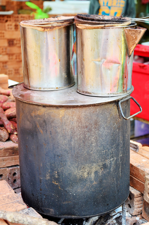 steel making: Stainless steel pot for making coffee and tea lao style on old stove at local restaurant in Pakse, Champasak, Laos.