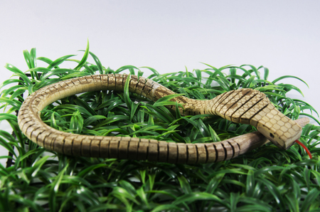 King cobra snake toy made from wooden on plastic grass
