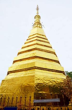 Glod chedi of Wat Phra That Cho Hae temple for people visit and pray in Phrae Province Thailand
