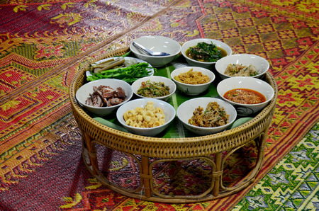 dinners: Khan tok or Khantoke dinners are a northern tradition thailand with Northern Thai sausage and Green chilli dip with boiled vegetables Stock Photo