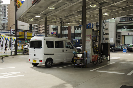 fill in: Japanese people drive van go to fill oil in petrol station at Shinjuku city on October 21, 2016 in Tokyo, Japan