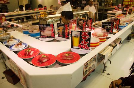 Japanese people and travelers foreigner eating sushi from sushi conveyor belt at japanese restaurant in Shinjuku on October 21, 2016 in Tokyo, Japan