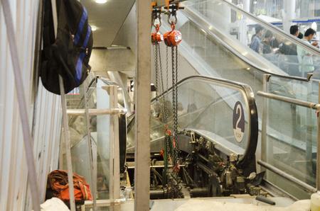 Thai professional mechanical people repair and maintenance change part of escalator at Suvarnabhumi international airport on December 11, 2016 in Bangkok, Thailand 版權商用圖片