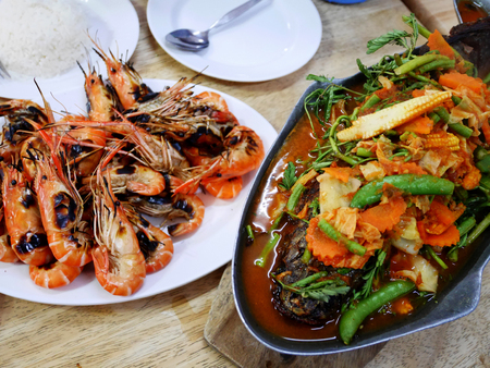 snakehead: Grilled prawns with seafood spicy sauce with Steamed whole fish with sauce or Snakehead with dressing in sour soup at restaurant thailand Stock Photo