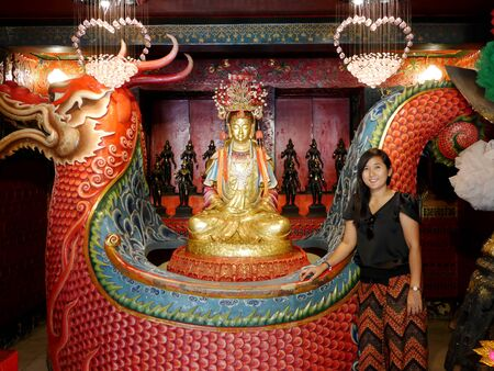 Thai woman posing with Chinese shrine of Lady princess Soi Dok Mak (Betel Nut Blossom) a local goddess for people praying in Wat Phanan Choeng temple at Ayutthaya, Thailand